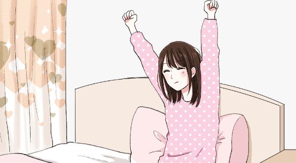 ベッドから起きて伸びをする女性