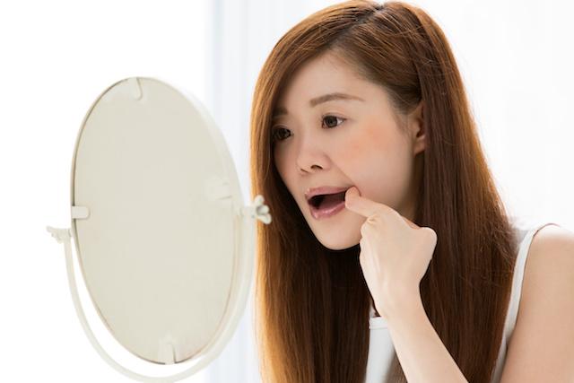 口元を指差す女性・鏡